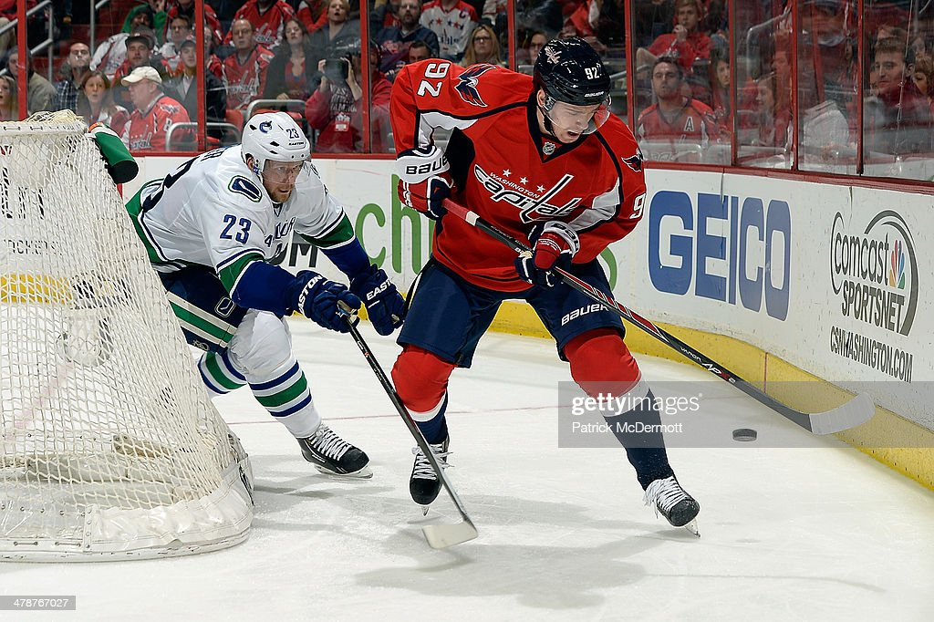 Evgeny Kuznetsov #92 of the Washington Capitals battles for the puck behind the net against <a gi-track='captionPersonalityLinkClicked' href=/galleries/search?phrase=Alexander+Edler&family=editorial&specificpeople=882987 ng-click='$event.stopPropagation()'>Alexander Edler</a> #23 of the Vancouver Canucks in the third period during an NHL game at Verizon Center on March 14, 2014 in Washington, DC.