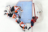Evgeny Kuznetsov of the Washington Capitals is checked into the goal by Brayden Schenn of the Philadelphia Flyers during the third period in Game One...