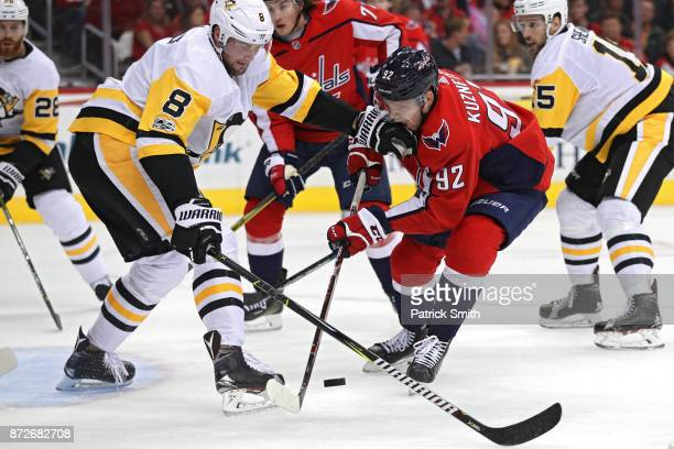 Evgeny Kuznetsov of the Washington Capitals is defended by Brian Dumoulin of the Pittsburgh Penguins during the second period at Capital One Arena on...