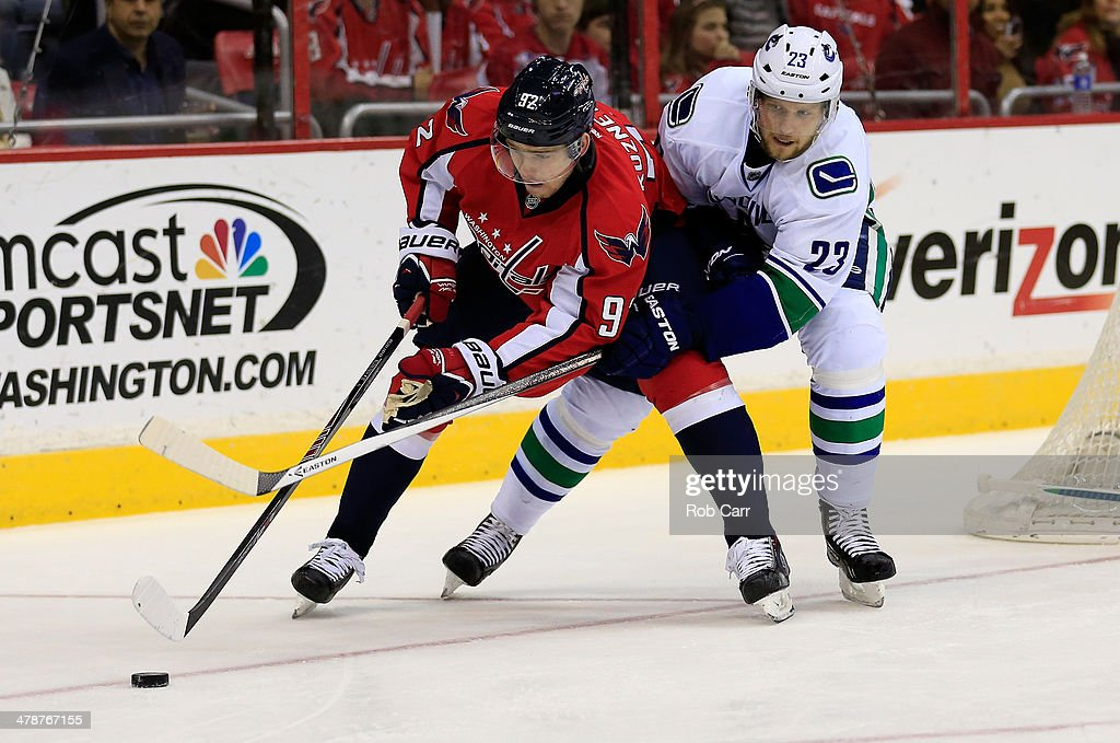 Evgeny Kuznetsov #92 of the Washington Capitals moves the puck in front of <a gi-track='captionPersonalityLinkClicked' href=/galleries/search?phrase=Alexander+Edler&family=editorial&specificpeople=882987 ng-click='$event.stopPropagation()'>Alexander Edler</a> #23 of the Vancouver Canucks during the third period of the Capitals 4-3 win at Verizon Center on March 14, 2014 in Washington, DC.