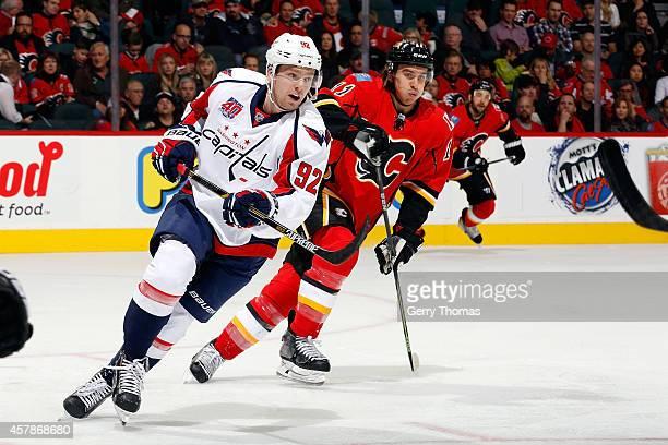 Evgeny Kuznetsov of the Washington Capitals skates against Mikael Backlund of the Calgary Flames at Scotiabank Saddledome on October 25 2014 in...