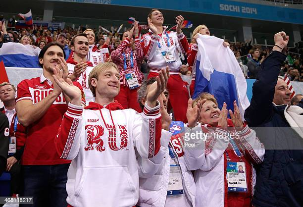 Evgeny Plyushchenko of Russia cheers with teammates as Yulia Lipnitskaya competes in the Team Ladies Free Skating during day two of the Sochi 2014...