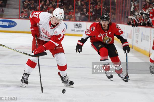 Evgeny Svechnikov of the Detroit Red Wings controls the puck against Erik Karlsson of the Ottawa Senators at Canadian Tire Centre on April 4 2017 in...