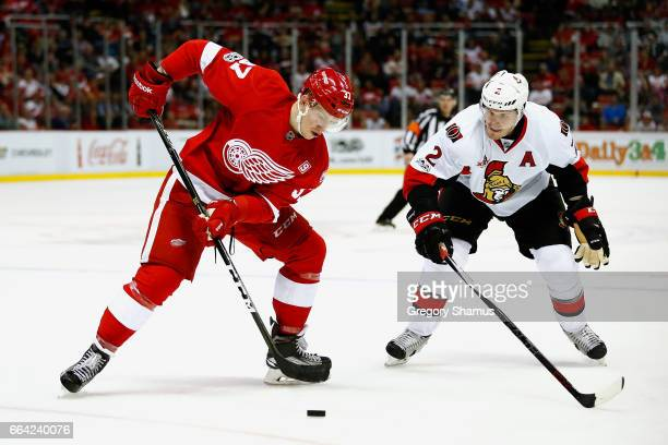 Evgeny Svechnikov of the Detroit Red Wings tries to control the puck next to Dion Phaneuf of the Ottawa Senators during the second period at Joe...