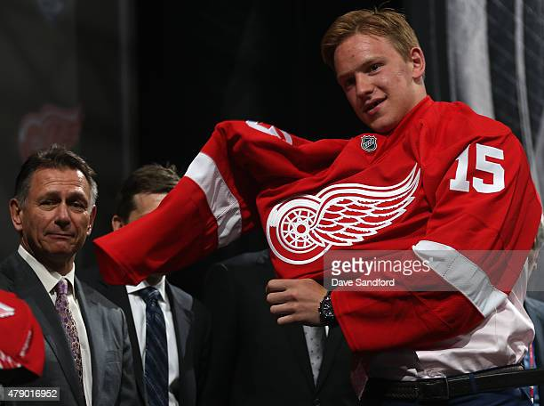 Evgeny Svechnikov puts on a jersey after being selected 19th overall by the Detroit Red Wings during Round One of the 2015 NHL Draft at BBT Center on...