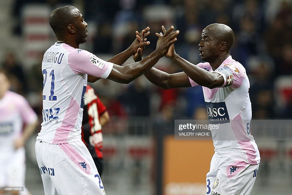 Evian's Cameroonian defender <a gi-track='captionPersonalityLinkClicked' href=/galleries/search?phrase=Dany+Nounkeu&family=editorial&specificpeople=6256951 ng-click='$event.stopPropagation()'>Dany Nounkeu</a> (R) celebrates after scoring a goal with Evian's Congolese defender <a gi-track='captionPersonalityLinkClicked' href=/galleries/search?phrase=Cedric+Mongongu&family=editorial&specificpeople=4305033 ng-click='$event.stopPropagation()'>Cedric Mongongu</a> (L) during the French L1 football match between Nice and Evian Thonon on April 4, 2015 at the Allianz Riviera stadium in Nice, southeastern France. AFP PHOTO / VALERY HACHE