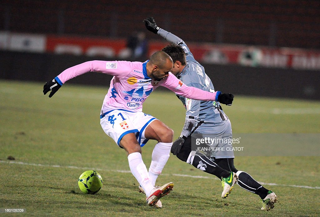 Evian's French defender Aldo Angoula (L) vies with Ajaccio's Roumanian forward Adrian Mutu during the French L1 football match Evian (ETGFC) vs Ajaccio (ACA) on January 26, 2013 at the city stadium Parc des sports in Annecy, eastern France.
