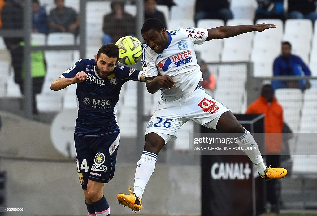 Evian's French midfielder Cedric Barbosa (L) vies with Marseille's Ivoirian defender Brice Dja Djedje (R) during the French L1 football match between Marseille and Evian Thonon Gaillard, on January 31, 2015 at the Velodrome stadium in Marseille, southern France. PHOTO / ANNE