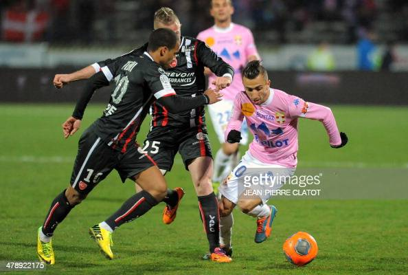 Evian's French midfielder Nicolas Benezet vies with Valenciennes' French midfielder Matthieu Dossevi during the French L1 football match EvianThonon...