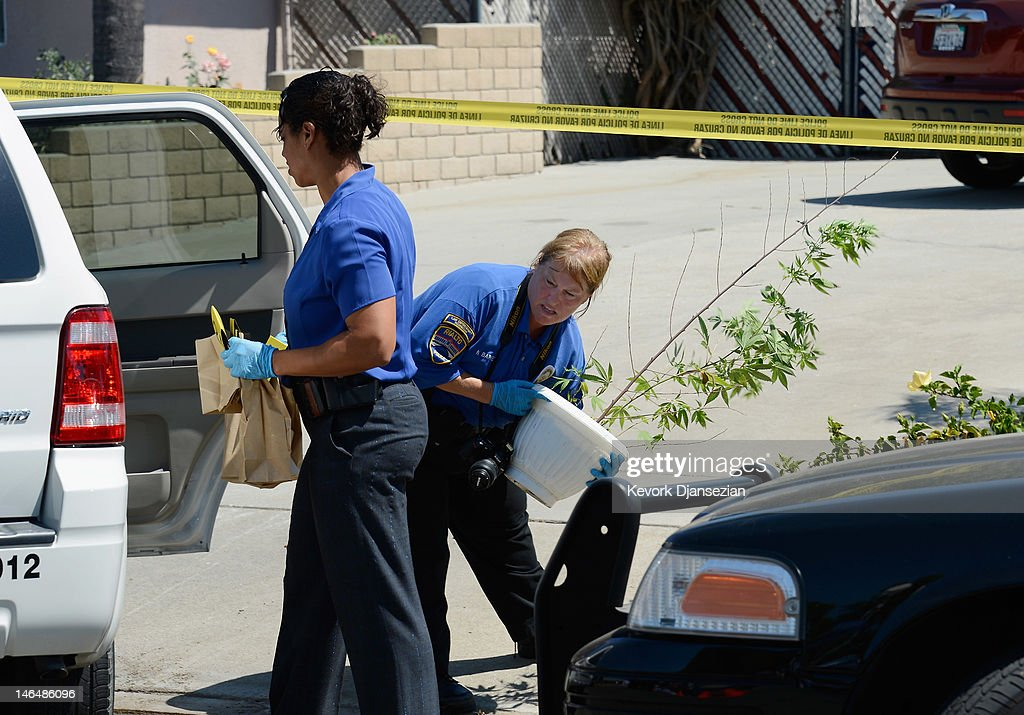Evidence from Rodney King's home is taken to a police car by Rialto Police detective Carla McCullough (L) as technician Noretta Barker carries a medicinal marijuana plant after the death of King on June 17, 2012 in Rialto, California. King, whose video beating by Los Angeles police in 1991 sparked riots after the acquittal of the four officers involved, was found dead at the age of 47 from an apparent drowning in his swimming pool.