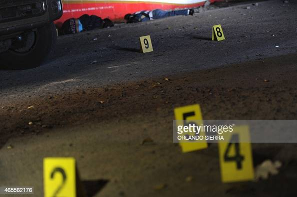 Evidence markers are placed near bodies at a crime scene where six people were murdered outside a bar in Tegucigalpa on March 7 2015 The World Health...