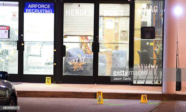 Evidence markers sit on the ground at the scene of a shooting in the parking lot of the Armed Forces Career Center/National Guard recruitment office...