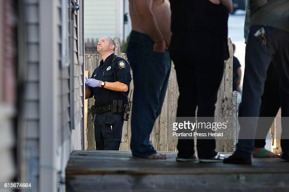 Evidence Technician Jon Reeder with the Portland Police Department examines a bullet hole in the window of an apartment house on Gilman Street on...