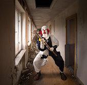 evil clown with a hammer standing in a broken corridor