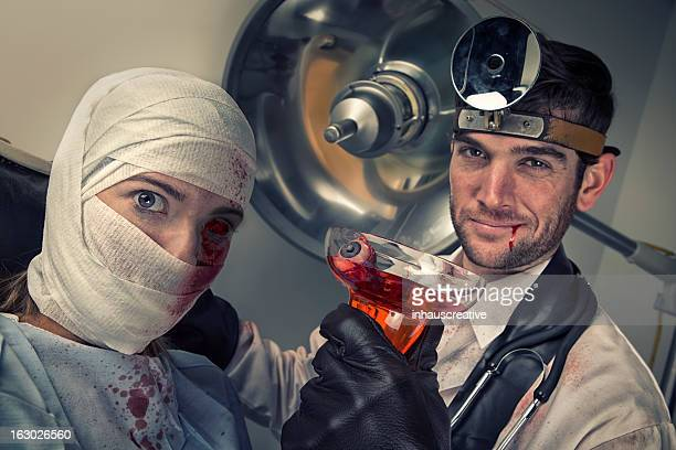 Evil Doctor drinking eyeball cocktail from shocked female victim