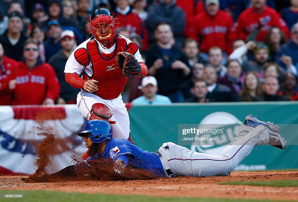 Evlis Andrus #1 of the Texas Rangers slides safely into home plate to score in the 8th inning past <a gi-track='captionPersonalityLinkClicked' href=/galleries/search?phrase=A.J.+Pierzynski&family=editorial&specificpeople=204486 ng-click='$event.stopPropagation()'>A.J. Pierzynski</a> #40 of the Boston Red Sox at Fenway Park on April 9, 2014 in Boston, Massachusetts.