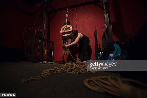 Evvy Apple ties up a voluntary submissive to suspend her at a dungeon party during the DomCon LA domination convention on May 21 2016 in Los Angeles...