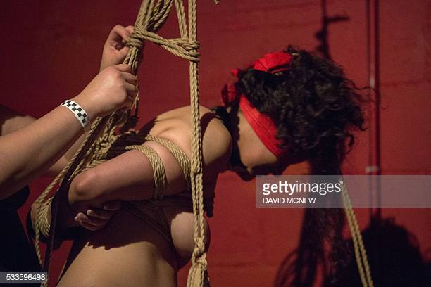 Evvy Apple ties up and suspends a voluntary submissive at a dungeon party during the DomCon LA domination convention on May 21 2016 in Los Angeles...