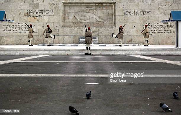 Evzone presidential guards perform ceremonial duties at the tomb of the unknown soldier near the Greek parliament building in Athens Greece on Monday...