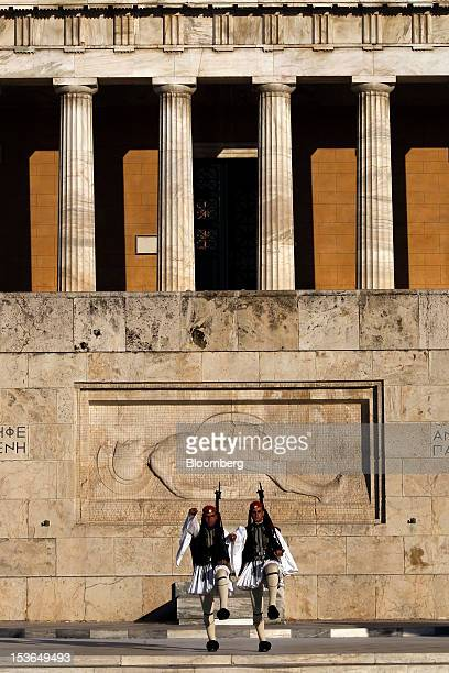 Evzone presidential guards perform ceremonial duties at the tomb of the unknown soldier in front of the Greek parliament building in Athens Greece on...