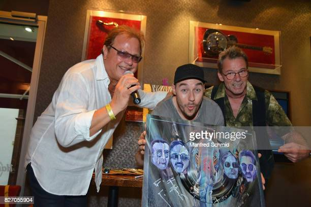 Ewald Pfleger of Opus painter Tom Lohner and Guenter Grasmuck of Opus pose during the 3rd birthday party of the Hard Rock Cafe Vienna on August 6...