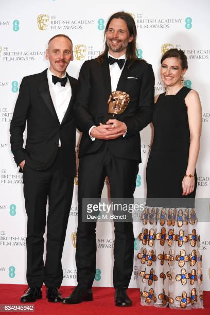 Ewen Bremner Linus Sandgren winner of the Cinematography award for 'La La Land' and Kelly Macdonald pose in the winners room at the 70th EE British...