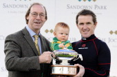 Ex Arsenal footballer Charlie George presents Tony McCoy and his son Archie pose with his trophy for being champion jockey at Sandown racecourse on...