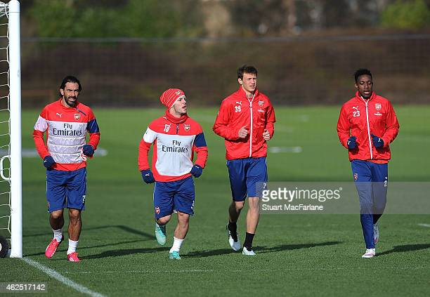 ex Arsenal player Robert Pires warms up with Jack Wilshere Krystian Bielik and Danny Welbeck before a training session at London Colney on January 30...