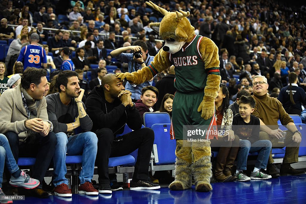 Ex Arsenal player <a gi-track='captionPersonalityLinkClicked' href=/galleries/search?phrase=Thierry+Henry&family=editorial&specificpeople=167275 ng-click='$event.stopPropagation()'>Thierry Henry</a> is greeeted by the Milwaukee Bucks mascot as Cesc Fabregas of Chelsea looks on ahead of the NBA match between New York Knicks and Milwaukee Bucks at O2 Arena on January 15, 2015 in London, England.