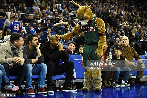 Ex Arsenal player Thierry Henry is greeeted by the Milwaukee Bucks mascot as Cesc Fabregas of Chelsea looks on ahead of the NBA match between New...