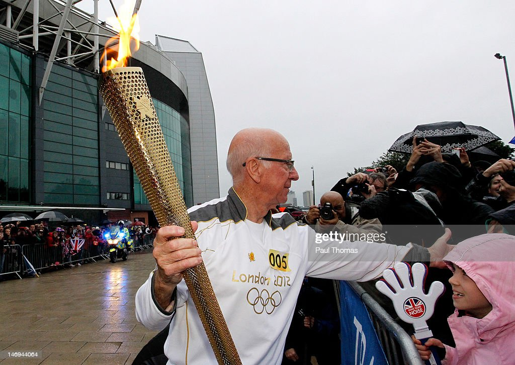 Ex Manchester United and England football player Sir Bobby Charlton carries the Olympic Flame on the Torch Relay leg between Salford and Leeds on June 24, 2012 in Manchester, England. The Olympic Flame is now on day 37 of a 70-day relay involving 8,000 torchbearers covering 8,000 miles.