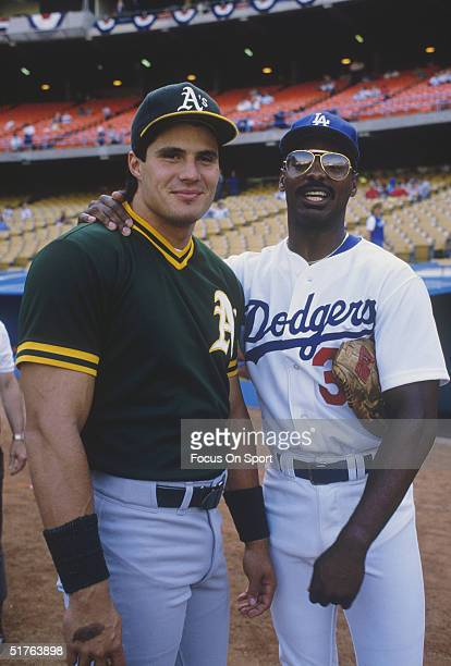 Ex teammates Jose Canseco of the Oakland Athletics and Mike Davis of the Los Angeles Dodgers pause for a photo during the World series at Dodger...