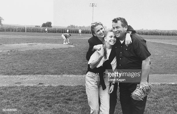 Exactor/selfproclaimed pres cand Tom Laughlin wearing baseball glove as he gets ganghugged by his daughters Teresa Kris at the Field of Dreams...