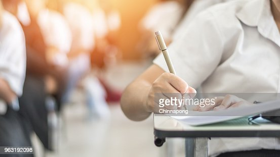 Exam with school student having a educational test, thinking hard, writing answer in classroom for  university education admission and world literacy day concept : Stock Photo