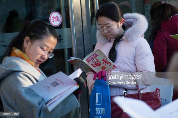 Examinees wait outside an exam site for the 2018 national civil servant exam on December 10 2017 in Taiyuan Shanxi Province of China Nearly 166...