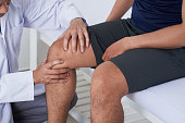 Doctor cheking knee of male patient