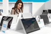 Woman choosing new laptop in electronics store