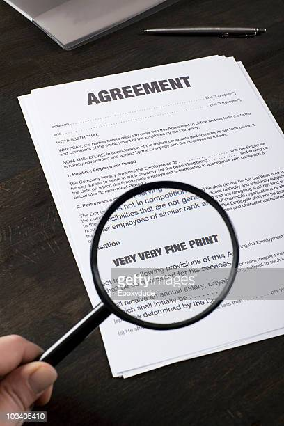 Examining the fine print of an employment agreement with a magnifying glass