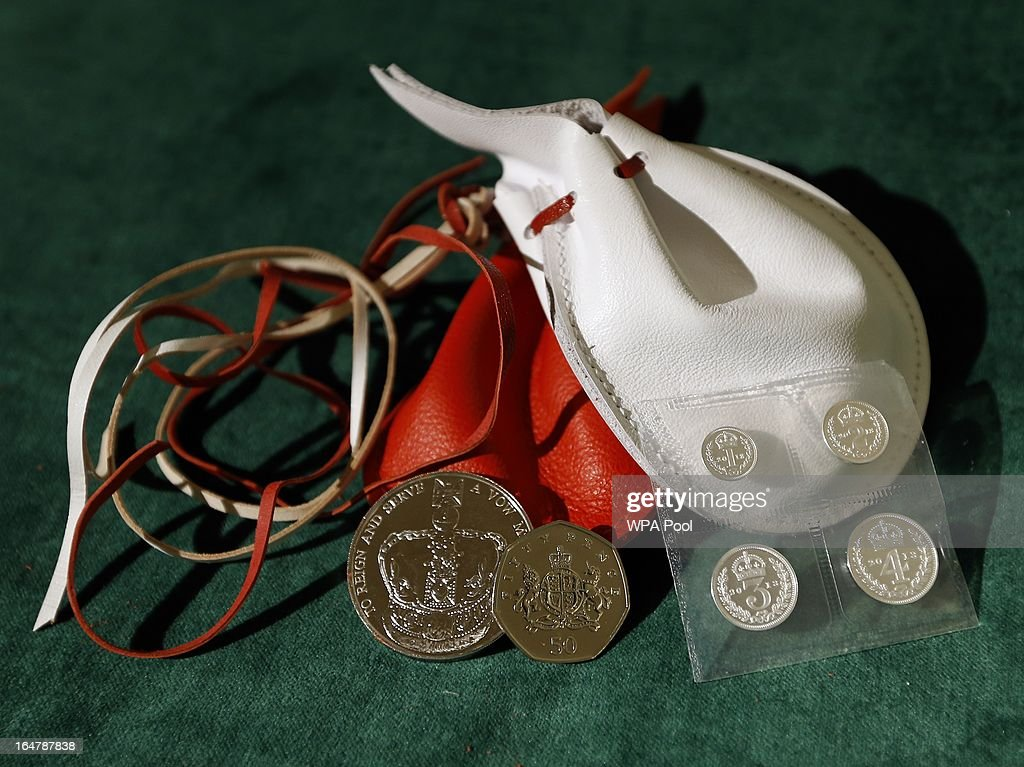 Examples of the two purses on display showing the coins that Britain's Queen Elizabeth II distributed during the Maundy service, at Christ Church Cathedral on March 28, 2013 in Oxford, England. The Maundy money was today distributed by the Queen to 87 women and 87 men, who each received two purses, one red and one white. A 5 GBP coin and 50 pence coin commemorating the 60th anniversary of The Queen's Coronation in the red purse. The white purse contains the uniquely minted Maundy Money. This takes the form of silver one, two, three and four penny pieces, the sum of which equals the number of years the Monarch's age.