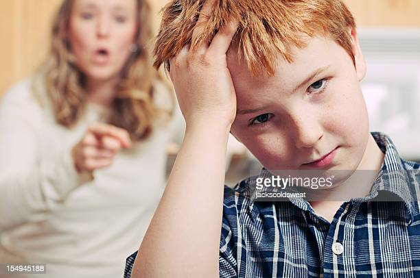 Exasperated young boy being scolded by his mother