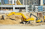 Work of excavating machine on building construction site