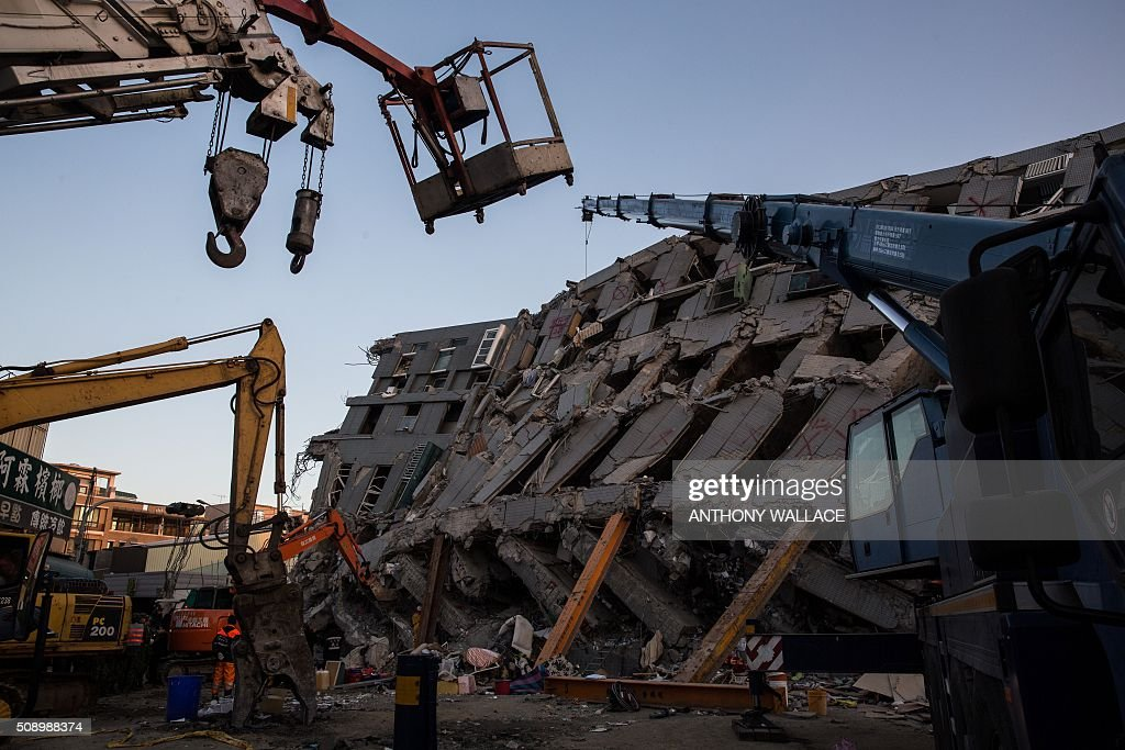 Excavation and construction vehicles are parked next to the remains of a building which collapsed in the 6.4 magnitude earthquake, in the southern Taiwanese city of Tainan on February 8, 2016. Rescuers raced on February 7 to free around 120 people buried under the rubble of an apartment complex felled by an earthquake in southern Taiwan that left 34 confirmed dead, as an investigation began into the collapse. AFP PHOTO / ANTHONY WALLACE / AFP / ANTHONY WALLACE
