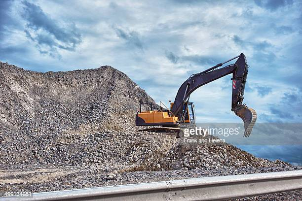 Excavator and mound of construction material