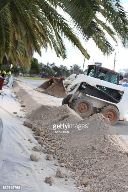 Excavator builds levee bank for flood mitigation