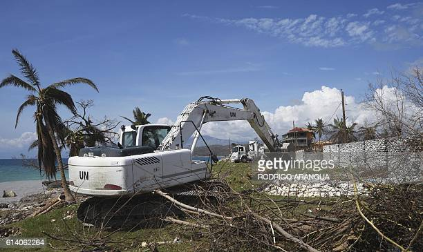 A UN excavator helps clear debris in Port Salut southwest of PortauPrince on October 11 2016 Haiti faces a humanitarian crisis that requires a...