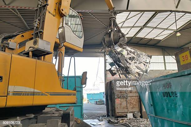 Excavator in a scrap metal recycling plant