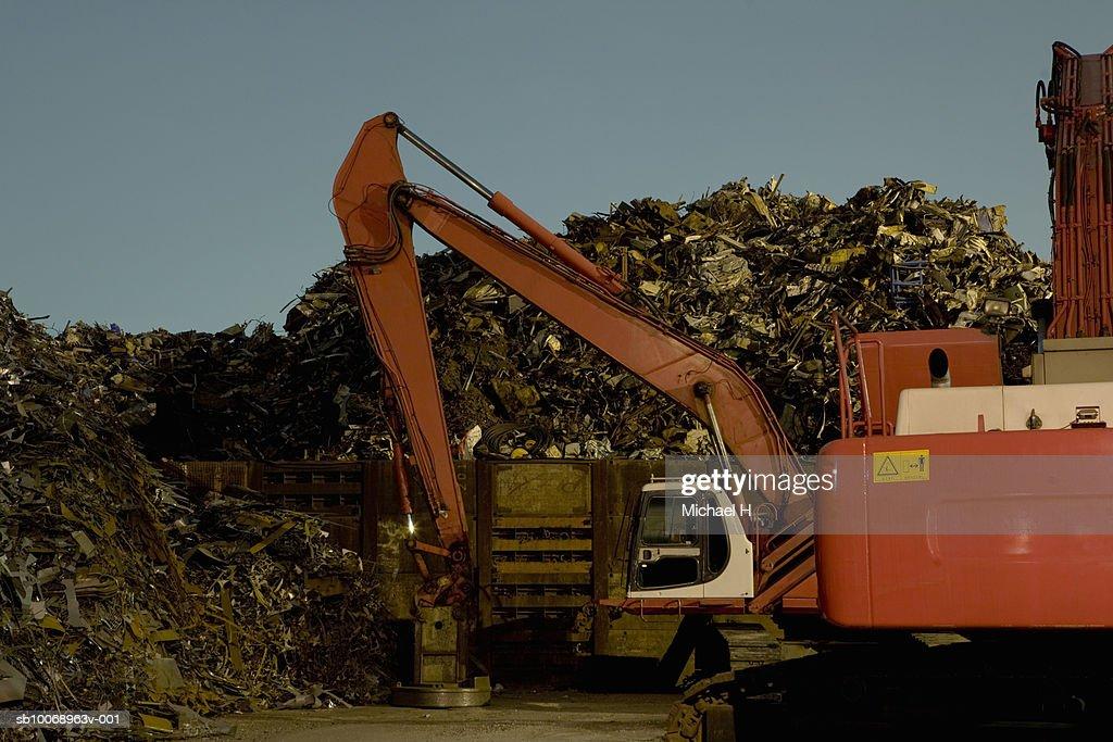 Excavator in junkyard at night : Stock Photo