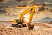 excavator loader machine during earthmoving works outdoors in sunset