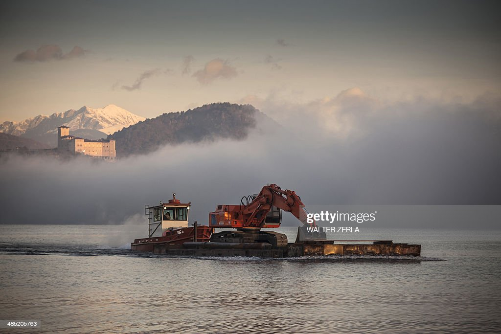 Excavator on barge,  Lake Maggiore, Varese, Piemonte, Italy