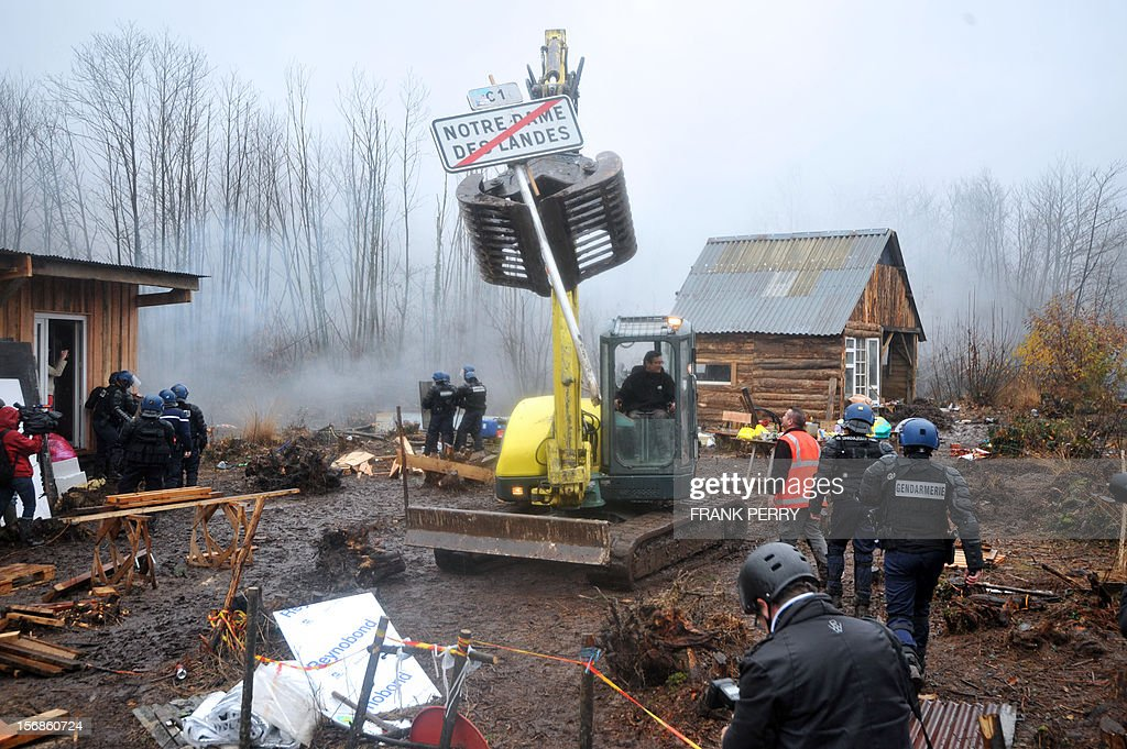 A, excavator removes 'Notre Dame des Landes ' sign as police forces stand guard after evacuating from the site squatters protesting against a project to build an international airport, in Notre-Dame-des-Landes, western France, on November 23, 2012. Two excavators and a large waste receptacle were deployed to clear an area where the protestors had set up shacks. The airport, which is scheduled to replace the current airport at Nantes in 2017, is a pet project of Socialist Prime Minister Jean-Marc Ayrault, who was the city's mayor from 1989 until this year.